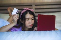 Młoda piękna szczęśliwa Azjatycka Japońska kobieta używa karta kredytowa interneta bankowość na laptopie w domu w łóżkowym uśmiec zdjęcie royalty free