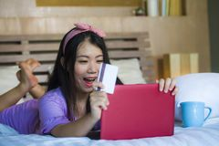 Młoda piękna szczęśliwa Azjatycka Japońska kobieta używa karta kredytowa interneta bankowość na laptopie w domu w łóżkowym uśmiec fotografia stock