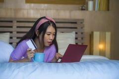 Młoda piękna szczęśliwa Azjatycka Japońska kobieta używa karta kredytowa interneta bankowość na laptopie w domu w łóżkowego zakup obraz stock