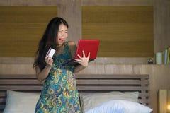 Młoda piękna szczęśliwa Azjatycka Japońska kobieta używa karta kredytowa interneta bankowość na laptopie w domu w łóżkowego zakup zdjęcie stock