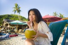 Młoda piękna, szczęśliwa Azjatycka kobieta 20s pije zrelaksowanego kokosowego sok na tropikalnej raj miejscowości nadmorskiej w s Obraz Stock