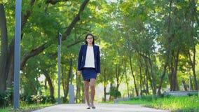 Młoda piękna szczęśliwa biznesowa kobieta chodzi w w formalnej odzieży i szkła zieleniejemy parkowy samotnego Dziewczyna utrzymuj zbiory wideo