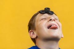 Młoda piękna szczęśliwa chłopiec z pieg koszulki mienia wiercipięta błękitnym kądziołkiem na żółtym tle zdjęcia stock