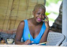 Młoda piękna, szczęśliwa czarna afro Amerykańska biznesowa kobieta w włosianym działaniu od miasto kawiarni opowiadać szczęśliwy  obrazy stock