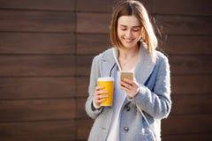 Młoda piękna szczęśliwa elegancka modniś dziewczyna z koktajlem, smoozy napojem i smartphone, zdjęcie royalty free