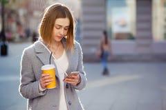 Młoda piękna szczęśliwa elegancka modniś dziewczyna z koktajlem, smoozy napojem i smartphone, obraz stock