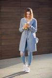 Młoda piękna szczęśliwa elegancka modniś dziewczyna z koktajlem, smoozy napojem i smartphone, zdjęcie stock