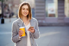 Młoda piękna szczęśliwa elegancka modniś dziewczyna z koktajlem, smoozy napojem i smartphone, obraz royalty free