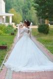 Młoda piękna szczęśliwa panna młoda z kwiatu bukietem w parku zdjęcie royalty free
