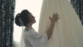 Młoda piękna szczęśliwa panna młoda przygotowywa w ranku dla ślubu, wiruje z ślubną suknią zdjęcie wideo