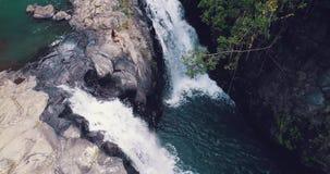 Młoda piękna turystyczna siedząca pobliska tropikalna siklawa zbiory wideo