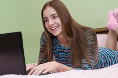 Młoda piękna uśmiechnięta kobieta używa laptopu lying on the beach na łóżku Zdjęcia Stock