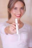 Młoda piękna uśmiechnięta kobieta wskazuje przed ona miesiączka bawełnianego tampon w zamazanym tle, zdjęcia stock