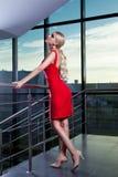 Młoda piękna wspaniała blondynki dziewczyna w czerwony smokingowy przyglądającym up w kierunku, pozujący blisko szklanej gabloty  Fotografia Stock