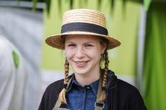 Młoda piękna wzorcowa przedstawienie dziewczyna ono uśmiecha się przy ulicą w słomianym kapeluszu Zdjęcie Royalty Free
