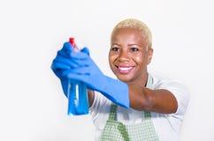 Młoda pięknego, szczęśliwego czarnego afrykanina amerykańska kobieta używa detergentową kiści butelkę jako i ho Zdjęcia Stock