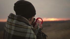 Młoda podróżnik dziewczyna zawijająca w szkockiej kracie relaksuje z filiżanką napój przy zmierzchem Samotność, wolność, samotnoś zbiory wideo
