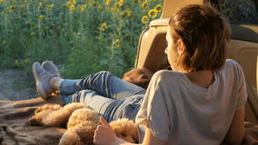 Młoda podróżnik kobieta z jej psem kłama w samochodu otwartym bagażniku zdjęcie wideo