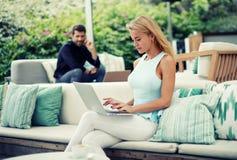 Młoda pomyślna biznesowej kobiety praca na laptopie podczas ranku śniadania, kobieta przedsiębiorca z jej książki obsiadaniem na  Zdjęcia Royalty Free