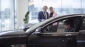 Młoda pomyślna para ogląda ufnego dziewczyny obsiadanie w kabinie nowy, drogi samochód na kierowcy siedzeniu, przy zbiory