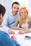 Młoda poważna para spotyka agenta nieruchomości Zdjęcie Stock