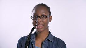 Młoda powabna amerykanin afrykańskiego pochodzenia kobieta ono uśmiecha się przy kamerą w szkłach, odizolowywającą nad białym tłe zbiory