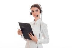 Młoda powabna biznesowa kobieta patrzeje oddaleni w mundurze z hełmofonami i mikrofon i robimy notatkom odizolowywać na bielu Obrazy Stock
