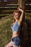 Młoda powabna blondynki dziewczyna z długie włosy w stajni na gospodarstwie rolnym blisko haystack w wsi z nęcić oczy jest ubrany Fotografia Royalty Free