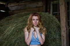 Młoda powabna blondynki dziewczyna z długie włosy w stajni na gospodarstwie rolnym blisko haystack w wsi z nęcić oczy jest ubrany Zdjęcie Royalty Free