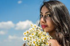 Młoda powabna brunetki dziewczyna z bukietem biali śródpolni chamomiles na lato słonecznym dniu Obrazy Royalty Free