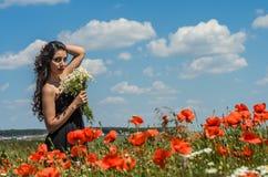 Młoda powabna brunetki dziewczyna z bukietem biali śródpolni chamomiles na lato słonecznym dniu Obraz Royalty Free