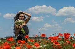 Młoda powabna brunetki dziewczyna z bukietem biali śródpolni chamomiles na lato słonecznym dniu Zdjęcia Royalty Free