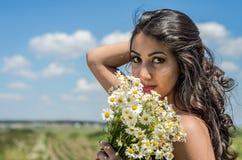 Młoda powabna brunetki dziewczyna z bukietem biali śródpolni chamomiles na lato słonecznym dniu Fotografia Stock