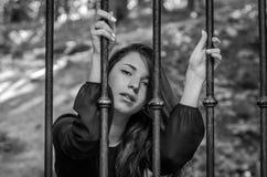 Młoda powabna dziewczyna nastolatek z długie włosy obsiadaniem za barami w więźniarskim więźniu w średniowiecznym więzieniu z smu Fotografia Stock