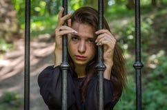 Młoda powabna dziewczyna nastolatek z długie włosy obsiadaniem za barami w więźniarskim więźniu w średniowiecznym więzieniu z smu Zdjęcie Royalty Free
