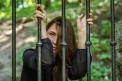 Młoda powabna dziewczyna nastolatek z długie włosy obsiadaniem za barami w więźniarskim więźniu w średniowiecznym więzieniu z smu Zdjęcia Royalty Free
