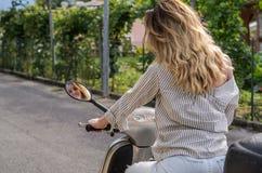 Młoda powabna dziewczyna z długie włosy przejażdżkami motocykl i spojrzenia przy jej odbiciem w rearview lustrze obraz stock