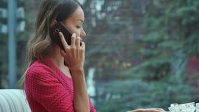 Młoda powabna kobieta dzwoni z komórka telefonem podczas gdy siedzący samotnie w sklep z kawą podczas czasu wolnego Zdjęcie Stock