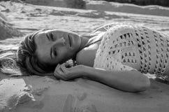Młoda powabna seksowna dziewczyna z długie włosy i makijaż w bikini kostiumu kąpielowym w erotycznym pozy lying on the beach i su Fotografia Royalty Free