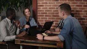 Młoda pozytyw grupa cztery mieszającego ścigającego się ludzie używa laptopy pastylki i smartphones siedzi przy miejsce pracy, wi zbiory