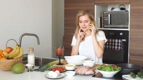 Młoda pozytywna dziewczyna, ostatnio dostawać zamężna, uczy się gotować do domu zrobił posiłkowi od świeżych i healthful dieta pr zbiory