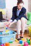 Młoda pracująca matka organizuje zabawki Zdjęcie Royalty Free