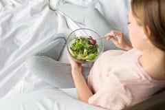 Młoda preganant kobieta oczekuje dziecka relaksuje na łóżku indoors zdjęcie royalty free