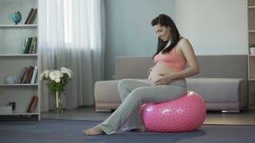 Młoda preggers dama słucha jej dziecko bicie, siedzi na sprawności fizycznej piłce zdjęcie wideo
