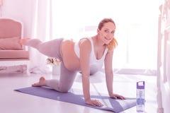Młoda promieniejąca długowłosa kobieta w ciąży w białej koszulce rozciąga jej nogę zdjęcie royalty free