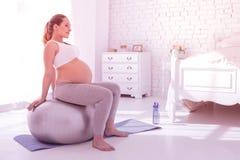 Młoda promieniejąca długowłosa kobieta w ciąży patrzeje koncentrujący w białej koszulce obraz royalty free