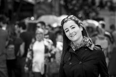Młoda przypadkowa kobieta ono uśmiecha się przy kamerą w ruchliwej ulicie obraz stock
