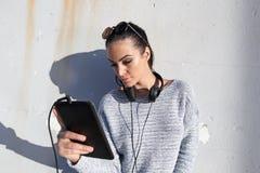 Młoda przypadkowa kobieta w pulowerze z hełmofonami i pastylką fotografia royalty free