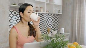 M?oda przypadkowa przygl?daj?ca kobieta siedzi, pij?cy kaw? i dzia?anie online zbiory