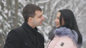 Młoda przystojna brunetki dziewczyna i jej chłopaka gawędzenie w parku Kochankowie stoją w parku i rozmowa, śmia się, całuje, zbiory